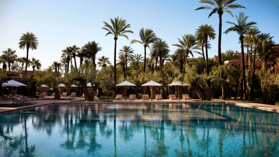 hotels in heaven royal mansour marrakech pool outdoor wooden loungers palm trees water sunny towels side view