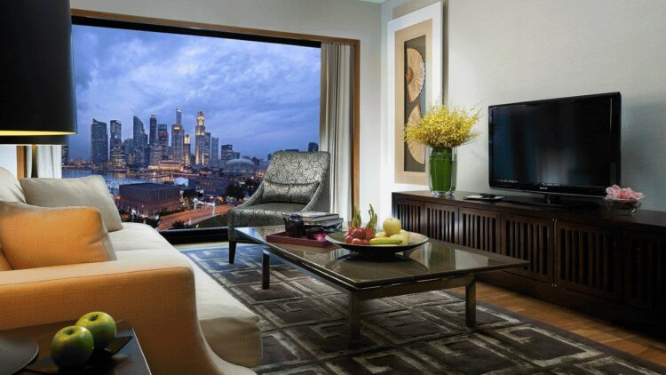 hotels in heaven mandarin oriental singapore living room view luxury television flowers vase skyline skyscrapers sofa cushions