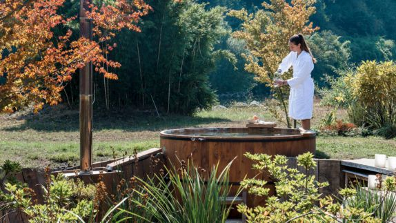Hot tubs at andBeyond Vira Vira hotels in heaven woman nature tree ggreen long hair luxury white bathrobe wood fruit lake outside candle spa