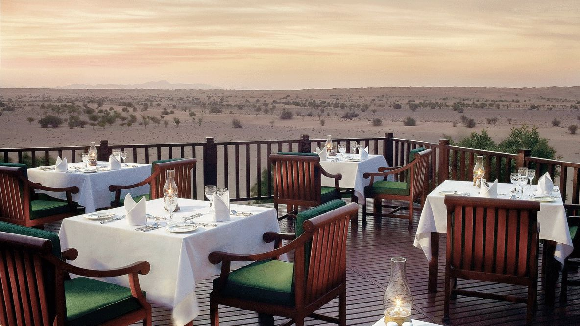 hotels in heaven al maha cuinary restaurant table chair view wasteland plants dishes tablecloth dinner dinning wood