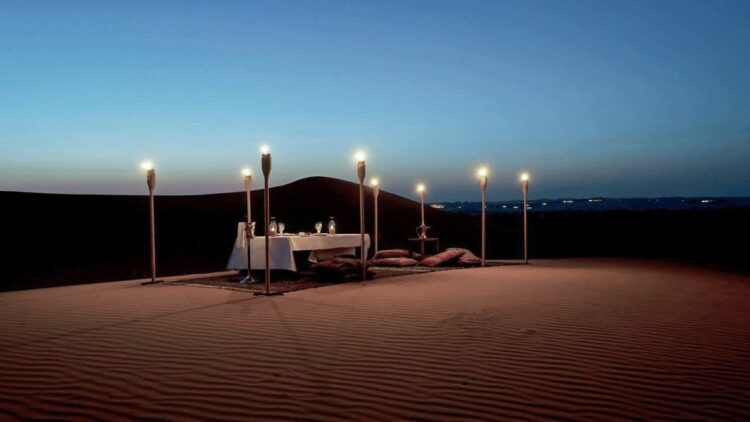 hotels in heaven al maha culinary desert dinner romantic lights dark table sand pillow carpet bottle glass view dishes hill