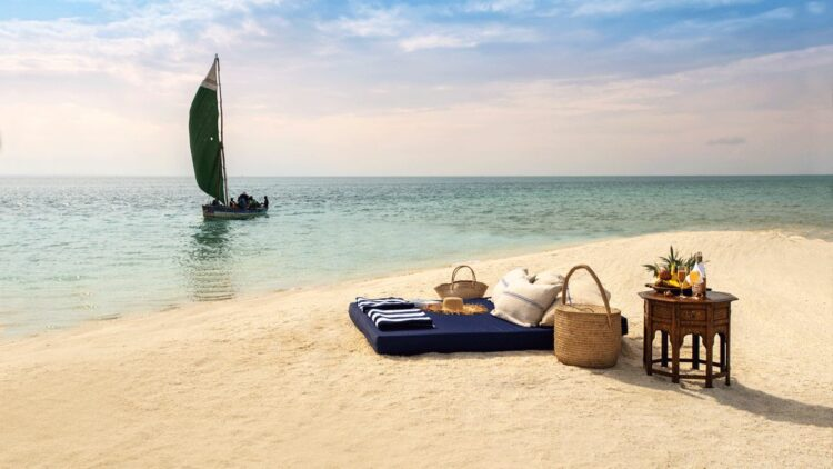 hotels in heaven andBeyond Benguerra Island Mozambique culinary beach picnic mattress fruits sparkling wine towel boat basket hat pillow sand sky
