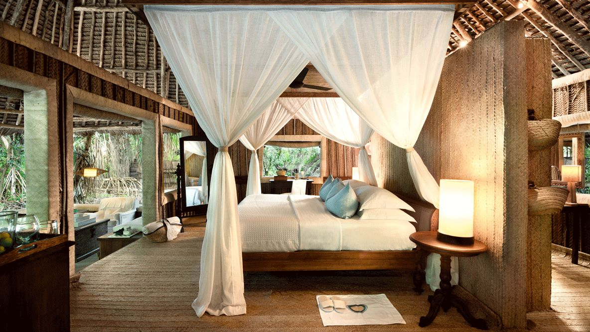 hotels in heaven andBeyond mnemba island lodge accommodation bedroom fourposter bed light pillow lake luxury mirror seats towel basket luxury