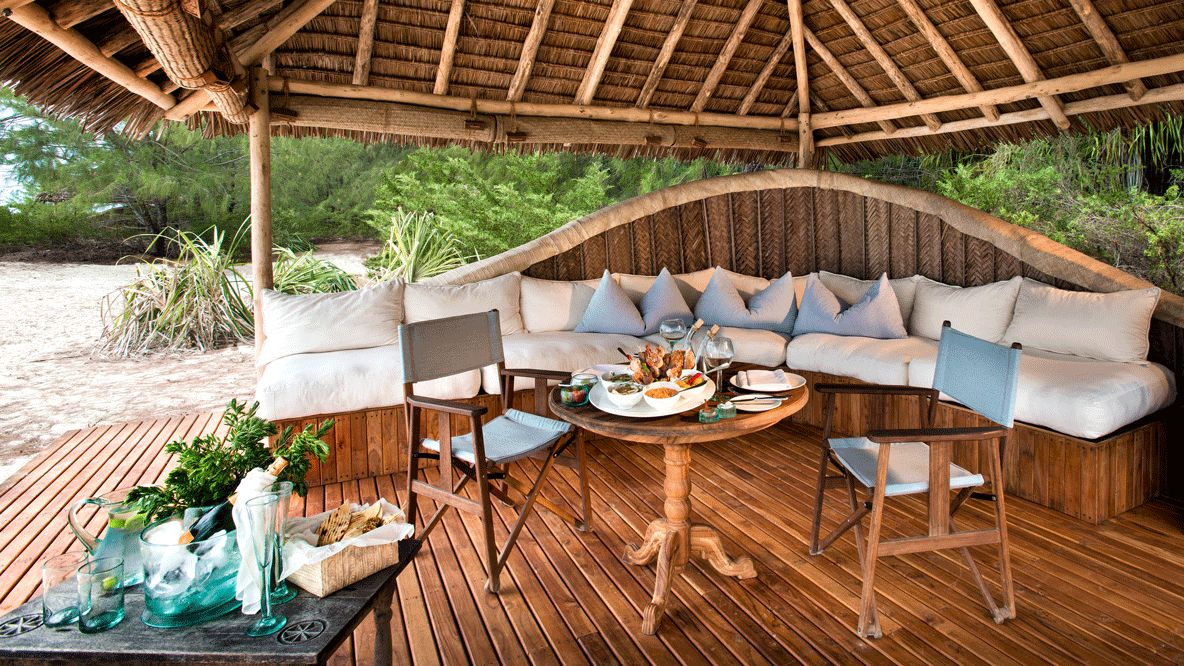 hotels in heaven andBeyond mnemba island lodge culinary breakfast food sparkling wine pillow seats chair couch wine glass napkin dishes table plants sand