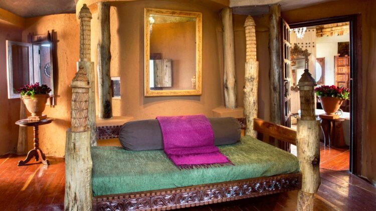 hotels in heaven and beyond andBeyond Ngorongoro Crater Lodge living room private suite pillow lake mirror wood vase flower window door plant couch