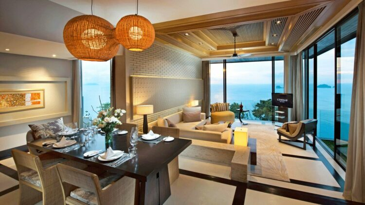 hotels in heaven accommodation livingroom koh samui table chair big window plate dishes napkin pillow tv couch luxury lamp view modern special sea sky flower painting glass