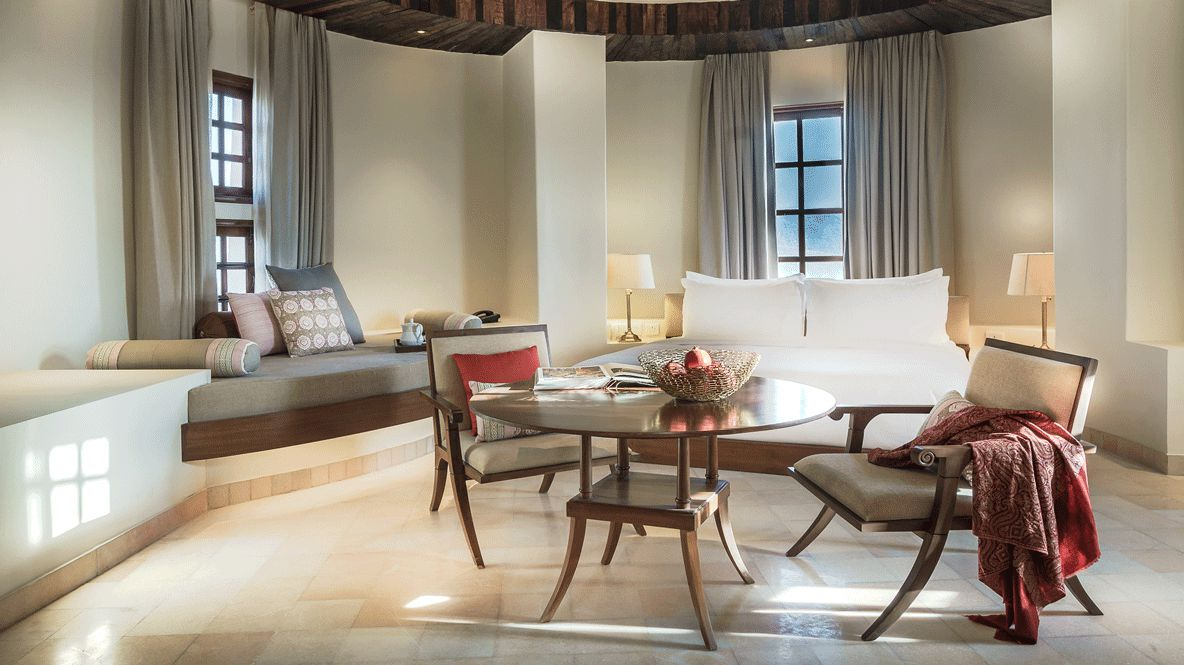 hotels in heaven Alila Fort Bishangarh bedroom living room suite chair table pillow bed fruits lamp book cozy blanket curtains luxury
