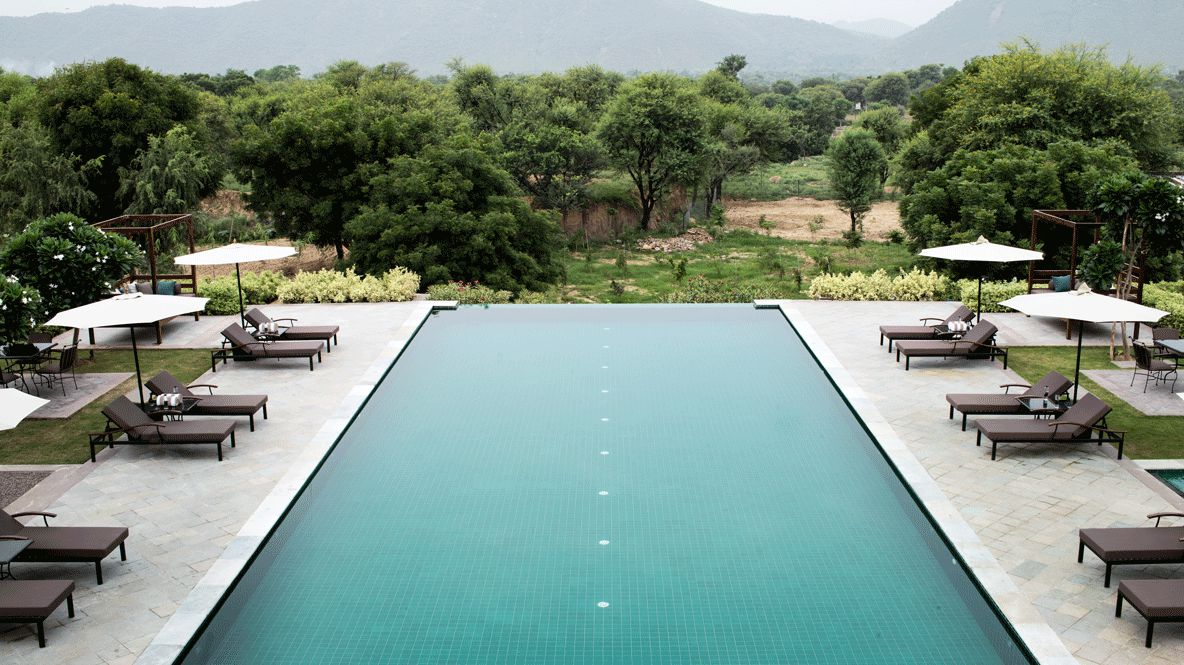 hotels in heaven Alila Fort Bishangarh pool spa luxury wellness deckchair tree view sunshade mountain hill nature table chair beautiful