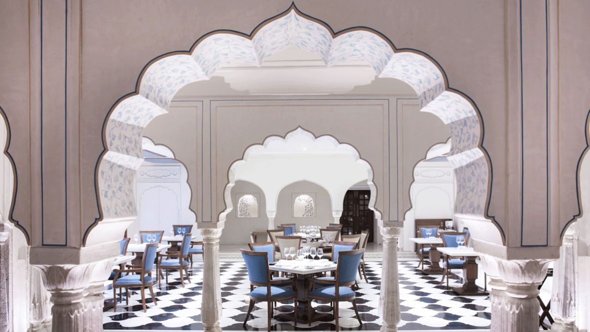 hotels in heaven Alila Fort Bishangarh restaurant food culinary inside luxury hotel dinner blue white chair table dishes wine glass door beautiful noble
