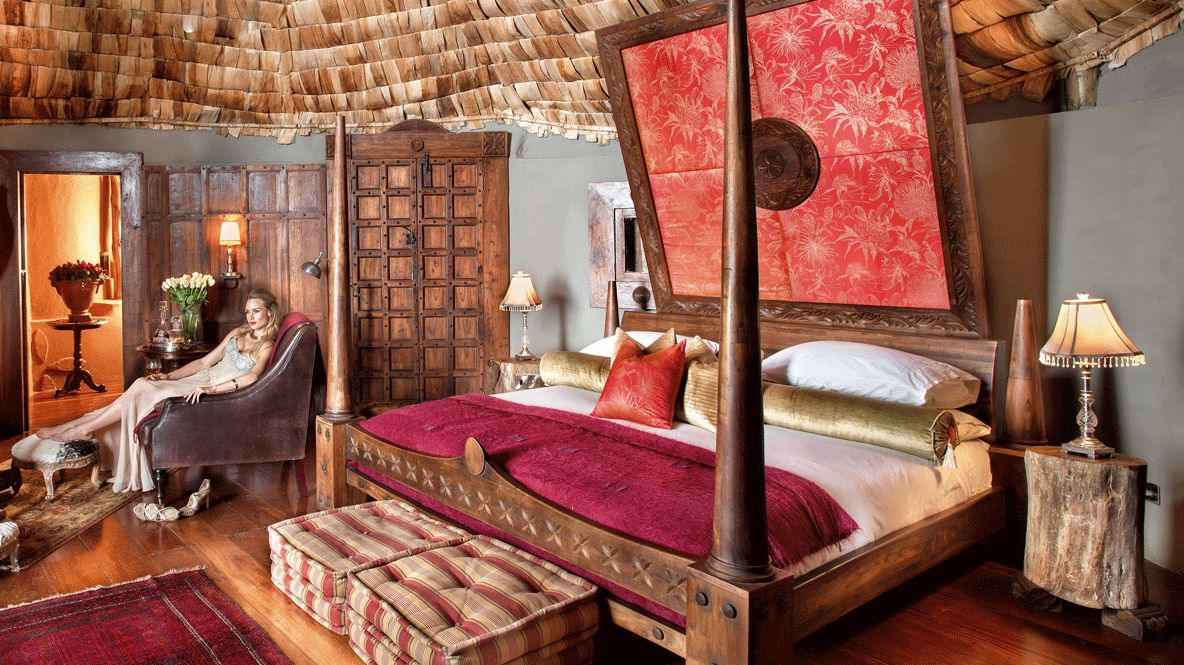 hotels in heaven and beyond andBeyond Ngorongoro Crater Lodge bedroom influencer woman bed pillow lake lamp beautiful rose flower wood luxury carpet seat high heels