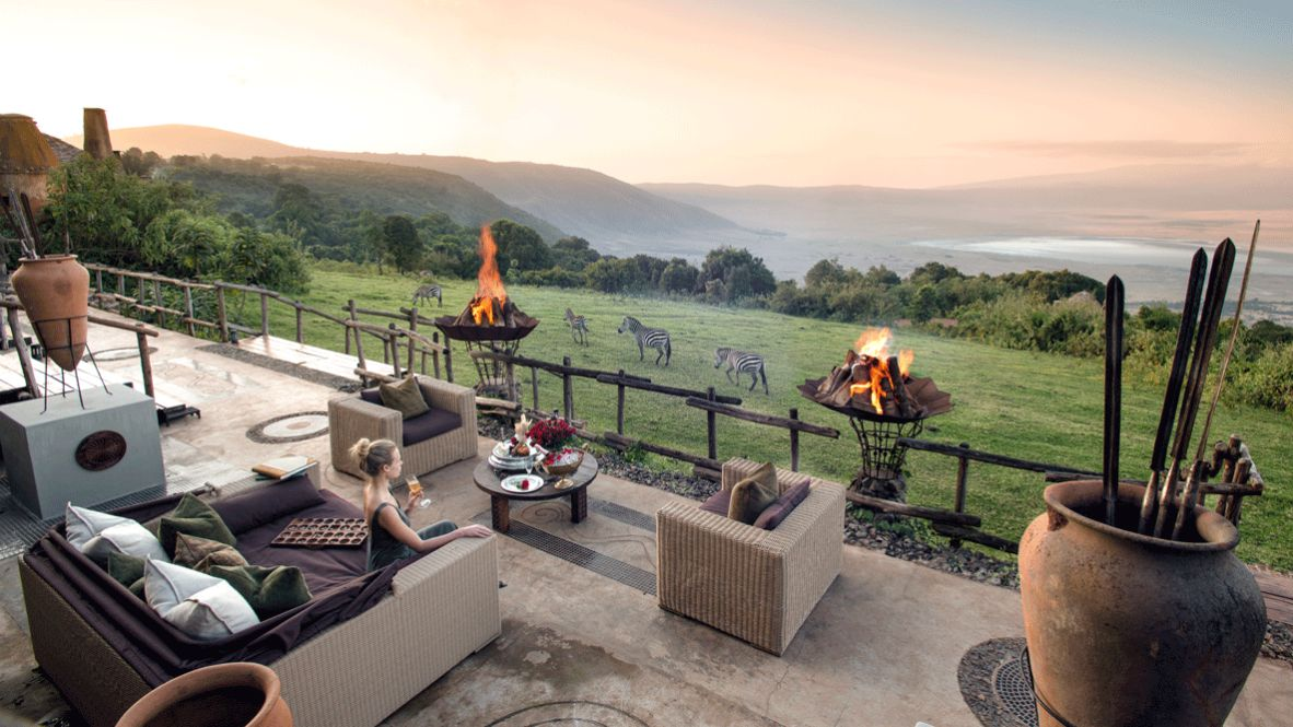 hotels in heaven and beyond andBeyond Ngorongoro Crater Lodge culinary view zebras woman fire Africa wild animals outside nature sunset couch drink bottle tree sparkling wine plate hills