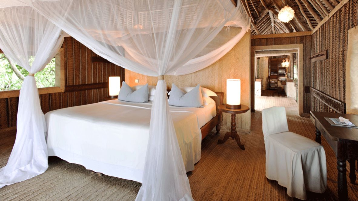 hotels in heaven andBeyond mnemba island lodge four post bed bed bedroom chair light wood pillow lake table magazine