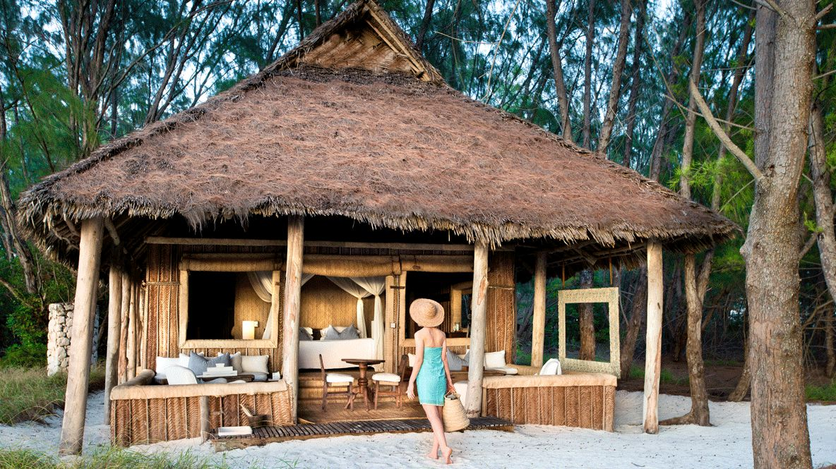 hotels in heaven andBeyond mnemba island lodge bungalow hut private suite pillow table chair woman towel bag sand tree lamp