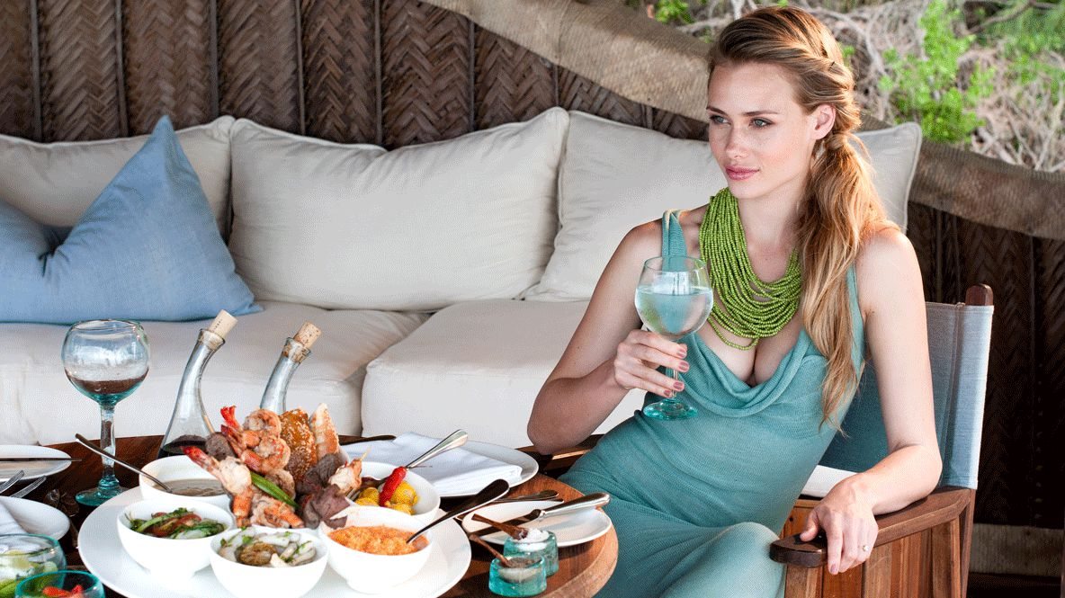 hotels in heaven andBeyond mnemba island lodge culinary influencer food beautiful woman pillow wine wine glass dishes lunch couch