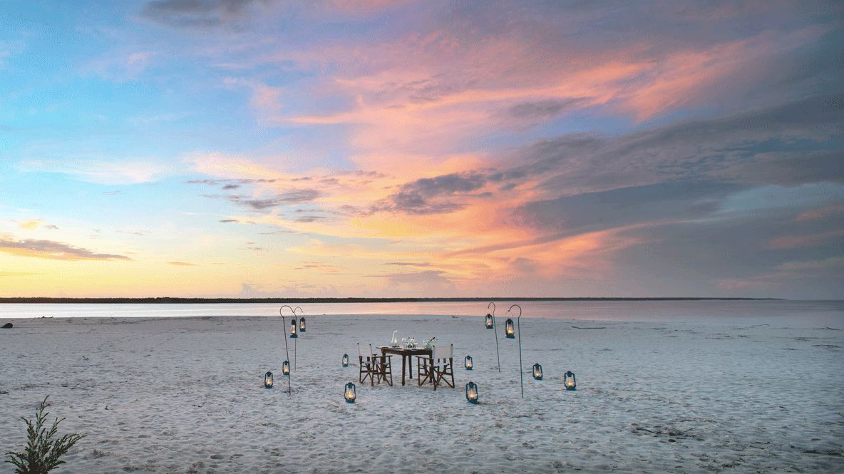 hotels in heaven andBeyond mnemba island lodge sunset oceanview culinary outdoor sand beach sea candle chair table bottle view