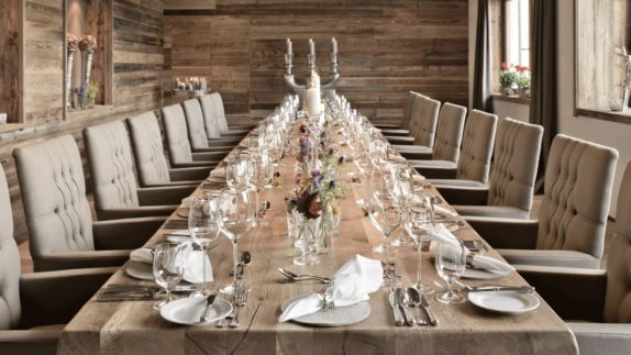 hotels in heaven hotel forsthofgut culinary restaurant wine glass long table plate cutlery dishes flower seats chair candle window decoration