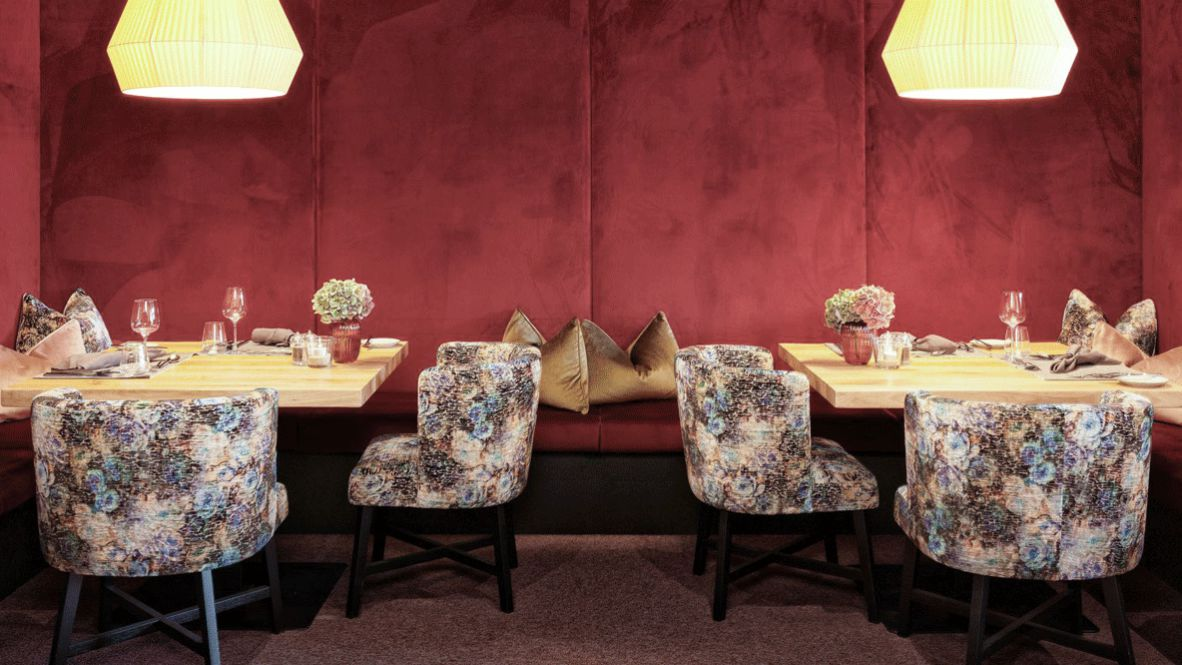 hotels in heaven hotel forsthofgut restaurant dining indoor exclusive dinner lights red pillow cozy table chair floral design flower wine glass candle napkin glass luxury noble