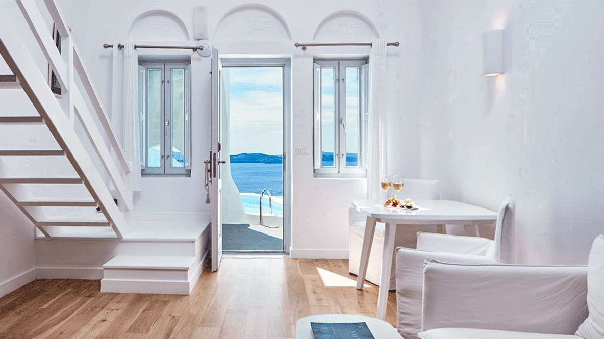 hotels in heaven katikies greece accommodation room with a view inside wine glass seats table stair white sea pool window beautiful luxury lamp door