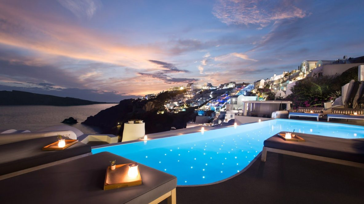 hotels in heaven katikies greece pool view location by night dark light pool beautiful view sea houses candle purple clouds deckchair