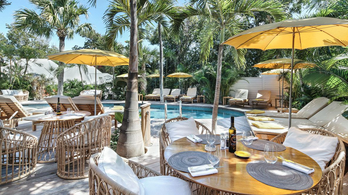 hotels in heaven villa marie saint barth pool culinary wine glass outside sunny wine deckchair napkin fork knife palm tree table seats with pillow cozy summer sunshade