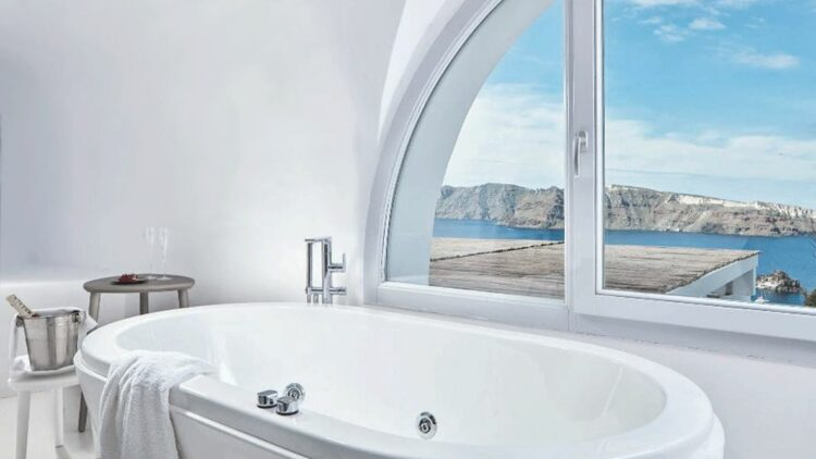 hotels in heaven katikies greece accommodation bathroom tub view white sparkling wine glasses table window sea sly clouds hills gangplank