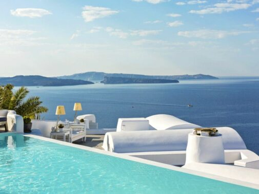 hotels in heaven katikies greece pool view terrasse luxury couch outside lamp view sea oat hill blue water sky clouds palm tree pillow