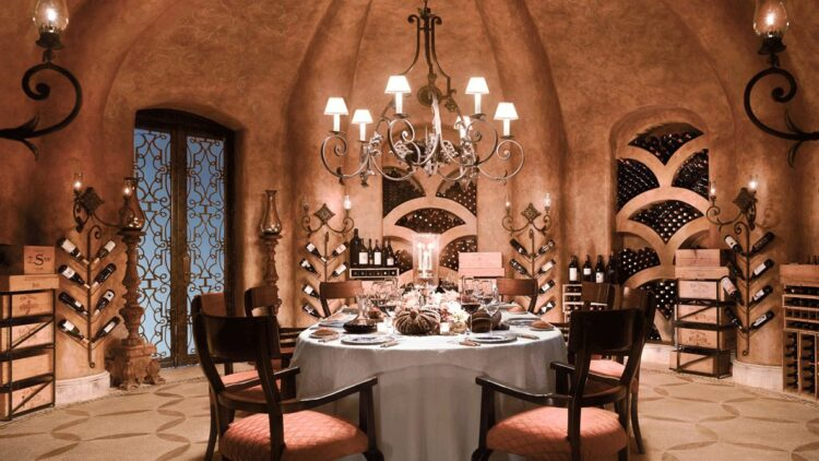hotels in heaven las ventanas al paraiso wine cellar culinary candle dinner wine bubble wine door dishes table chair bottles lights tablecloth romantic