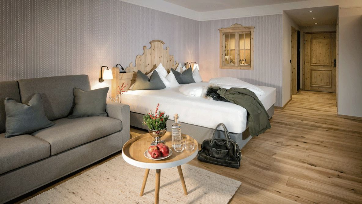 hotels in heaven hotel forsthofgut suite bed pillow couch lake apple fruits water jacket door carpet plants luxury glass Austria light