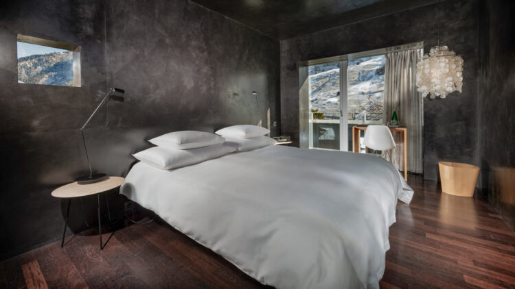 hotels in heaven 7132 location bedroom big bed white blanket pillows stone walls lamps table dark modern view outside