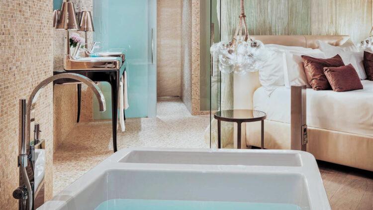 hotels in heaven aguas de ibiza suite luxury bathroom bathtub tab water luxurious bed bedroom sink table nightstand lamp