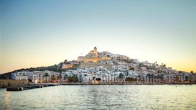 hotels in heaven aguas de ibiza location city skyline view white houses housefront lights evening sunset water sea little waves