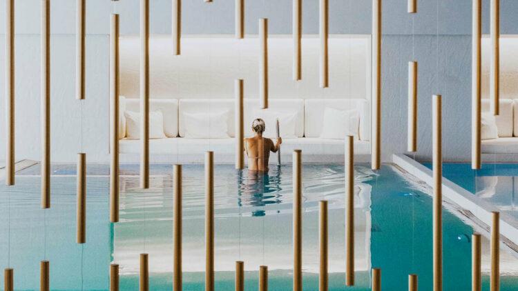 hotels in heaven aguas de ibiza spa pool influencer water poolside woman bathing suit bikini swimming relaxing sofa pillows