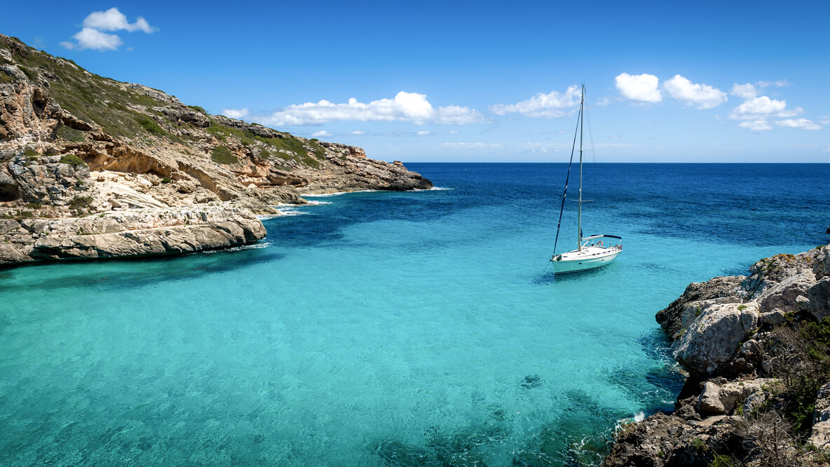 hotels in heaven agua de ibiza location ocean rocks rocky water turquoise ocean boat sailing sky clouds beautiful