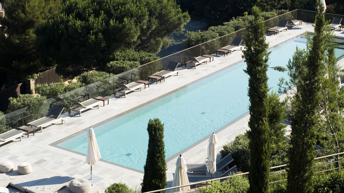 hotels in heaven La Reserve Ramatuelle outdoor pool lounger water trees sun shades sunny beautiful fence stone path swimming relaxing