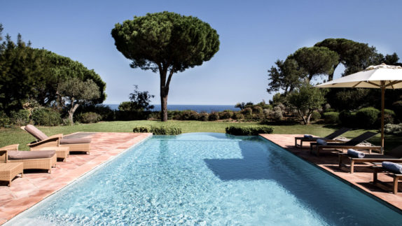 hotels in heaven La Reserve Ramatuelle outdoor pool ocenview lounger pillows trees shadows water turquoise bushes