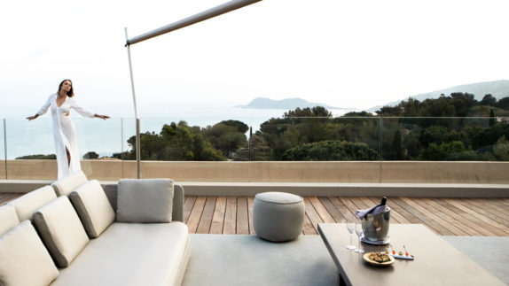 hotels in heaven La Reserve Ramatuelle terrasse dining with a view influencer woman white dress windy sofa cushions