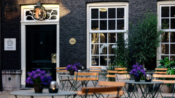 hotels in heaven the dylan amsterdam front courtyard accommodation culinary big windows flowers door outside lovely chairs plants
