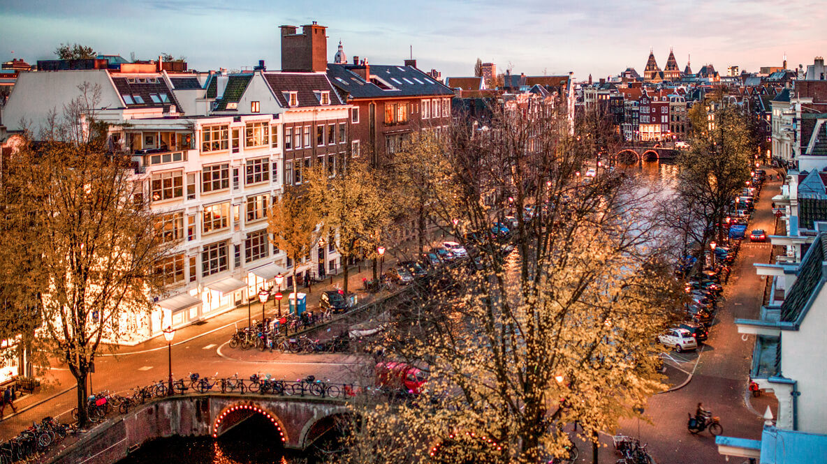 hotels in heaven the dylan amsterdam sunset view city life bicycles cars street bridge water river evening roofs