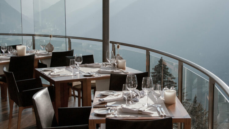 hotels in heaven miramonti boutique panorama restaurant view foggy day chairs table glasses wine candles napkins vase balcony