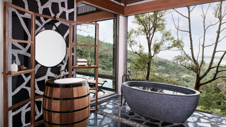 hotels in heaven keemala tub with a view trees mirror bathtub stone black outside sky barrel sink shelf chair
